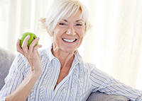 Woman with an apple after getting Immediate Function back after the Minimally Invasive All on 4 Implant Treatment by her Dallas oral surgeon at BiteLock.
