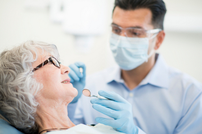 Woman getting a dental exam by the dentist to determine if they are a candidate for Dental Implants - Are You a Dental Implant Candidate? Bite Lock Teeth in a Day has the solution you!
